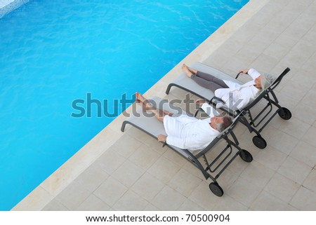Senior couple relaxing in long chairs - stock photo