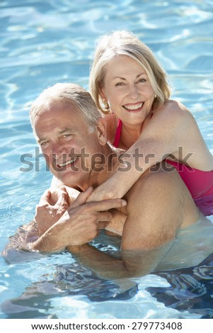 Senior Couple Relaxing In Swimming Pool Together - stock photo