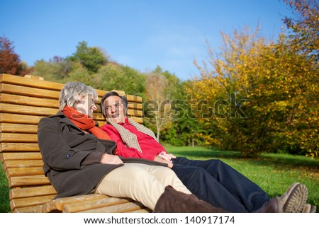 Senior couple relaxing in the autumn sun reclining side by side on a comfortable curved wooden bench in a park or garden - stock photo