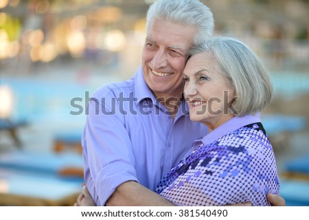 Senior couple relaxing near pool at hotel resort - stock photo