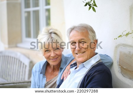 Senior couple relaxing on bench by the house - stock photo