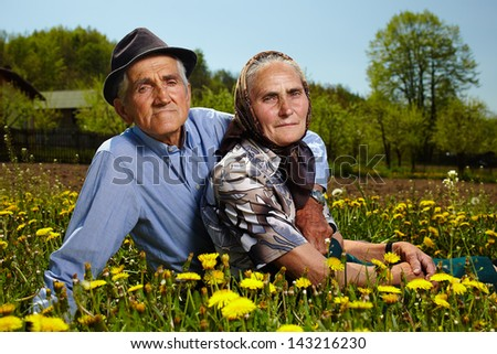 Senior couple resting in a dandelion field in the countryside - stock photo