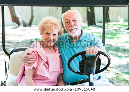 senior couple riding around in a golf cart.
