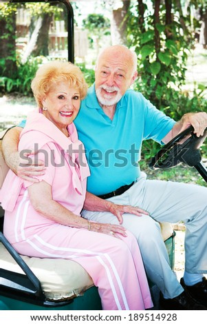 Senior couple riding around in an environmentally friendly golf cart.  - stock photo