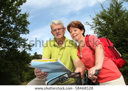 Senior couple riding bicycle in countryside with map - stock photo