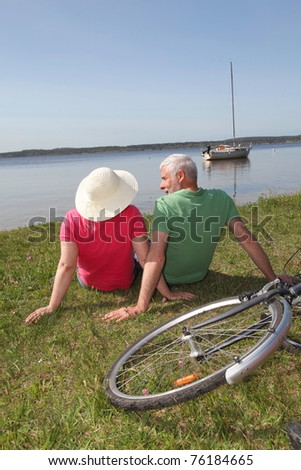 Senior couple riding bicycle in summer - stock photo