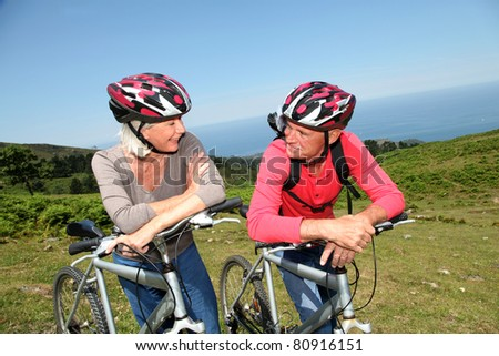 Senior couple riding mountain bikes in natural landscape