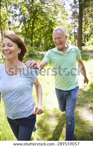 Senior Couple Running In Summer Countryside