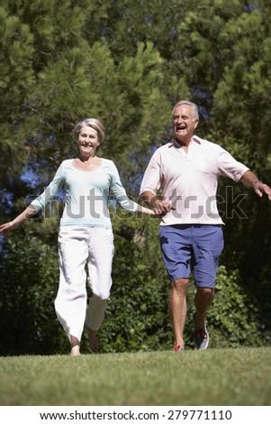Senior Couple Running Through Summer Field - stock photo