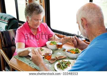 Senior couple says a prayer over a healthy turkey dinner served in the kitchen of their mobile home. - stock photo