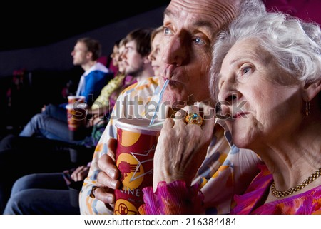 Senior couple sharing drink in cinema, close-up - stock photo
