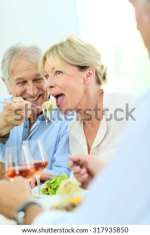 Senior couple sharing pasta at lunch time - stock photo
