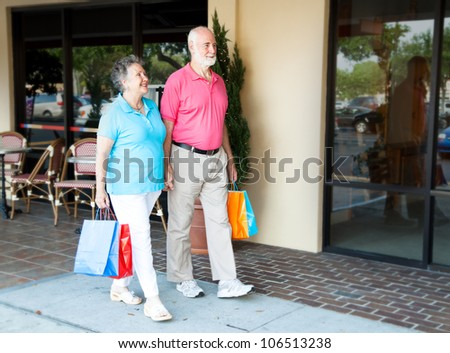 Senior couple shopping together at an outdoor mall. - stock photo
