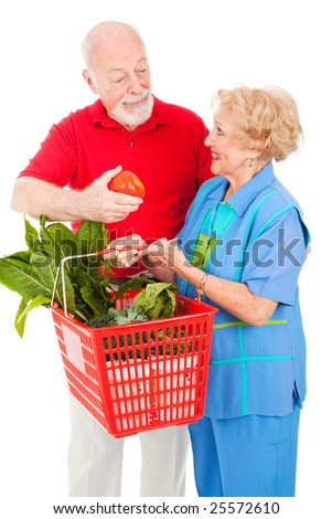 Senior couple shops for organic produce.  The husband offers the wife a tomato.  Isolated on white.