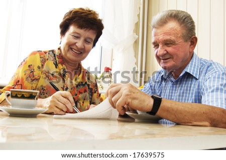 Senior couple signing document in home - stock photo