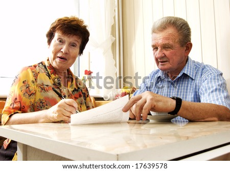 Senior couple signing document in home. Surprised woman - stock photo