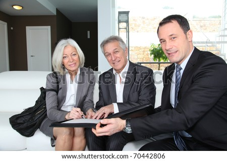 Senior couple signing financial contract for property purchase - stock photo