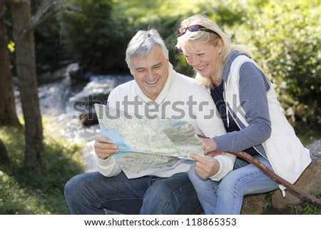 Senior couple sitting by river and looking at map