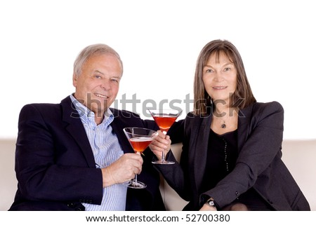 Senior couple sitting in a sofa with drinks