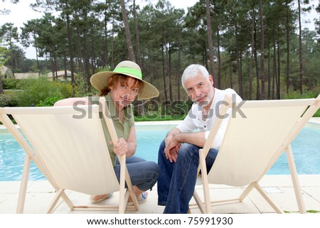 Senior couple sitting in deckchairs by a pool - stock photo