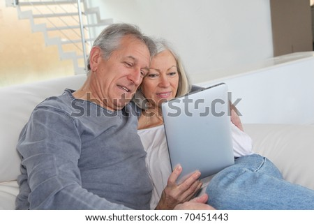 Senior couple sitting in sofa with electronic tablet - stock photo
