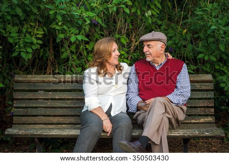 Senior couple sitting on a bench in Spain. They are 75 years old - stock photo