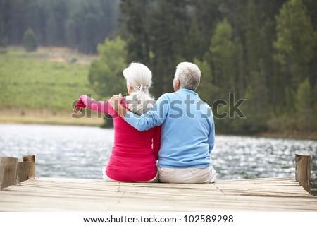 Senior couple sitting on a jetty - stock photo
