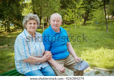 Senior couple sitting on a park bench.  Elderly couple relaxing outdoors on a summer day. - stock photo