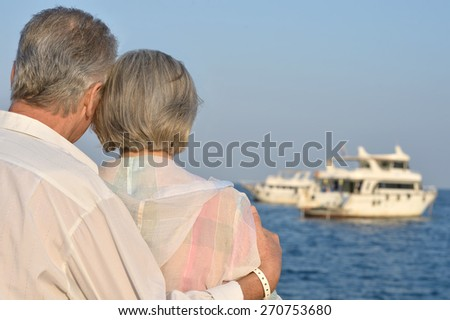Senior couple sitting on a rock looking a sea