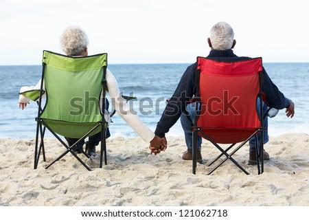 Senior Couple Sitting On Beach In Deckchairs - stock photo