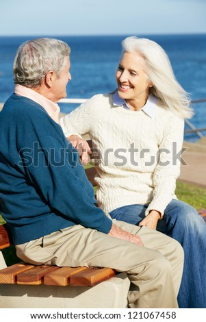 Senior Couple Sitting On Bench By Sea Together - stock photo