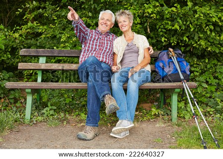 Senior couple sitting on bench during hiking trip in nature