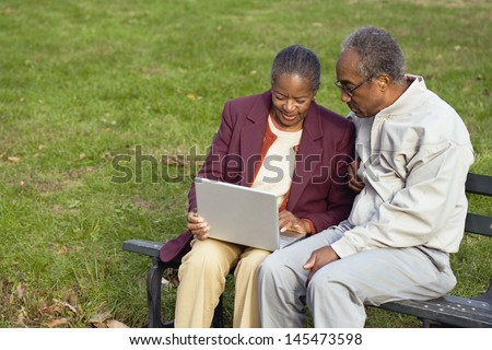 Senior couple sitting on bench with laptop