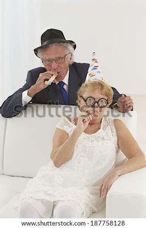 Senior couple sitting on couch wearing party hats celebrating  in living room  - stock photo