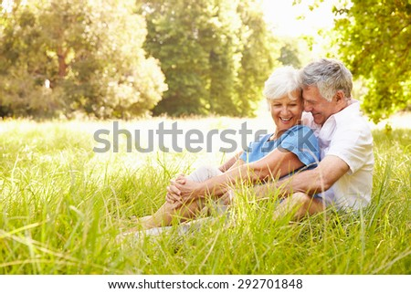 Senior couple sitting on grass together relaxing