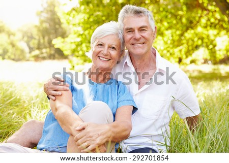 Senior couple sitting on grass together relaxing - stock photo