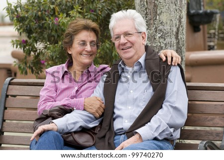 Senior Couple Sitting On Park Bench Outdoor - stock photo
