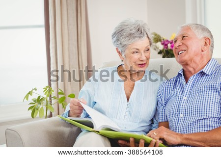 Senior couple sitting on sofa and reading a book in living room - stock photo