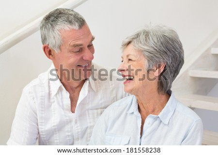 Senior couple sitting on stairs smiling at each other at home in living room - stock photo