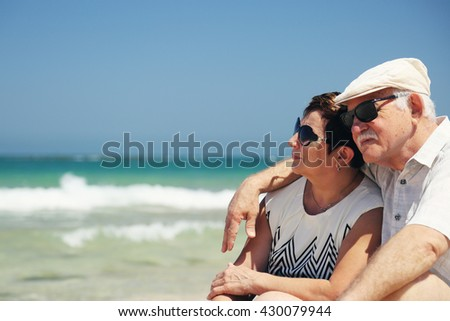 senior couple sitting on the beach