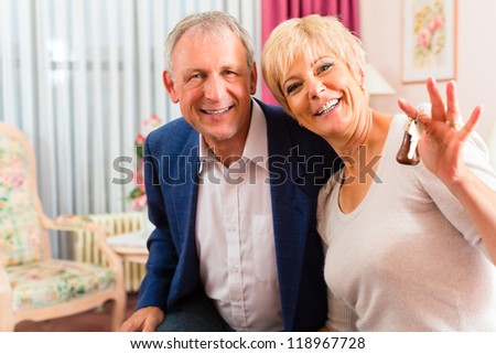Senior couple sitting on the bed in the hotel room and the woman has a key in her hand - stock photo
