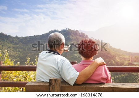 senior couple sitting on the bench looking the nature view - stock photo