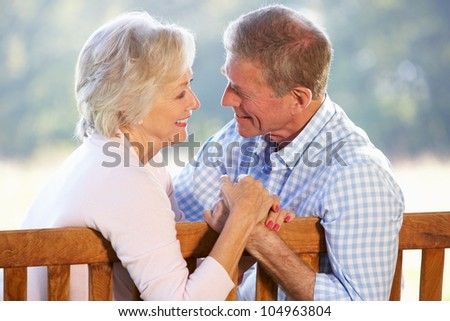 Senior couple sitting outdoors - stock photo