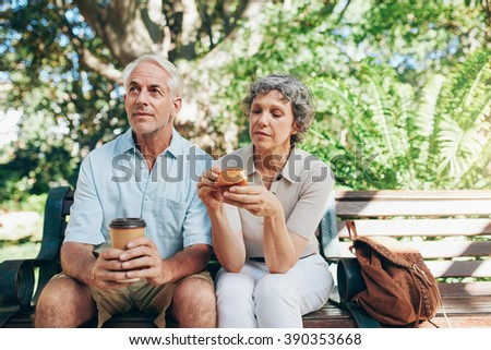 Senior couple sitting outdoors on a park bench drinking coffee and eating muffin. Tourist relaxing on a park bench. - stock photo