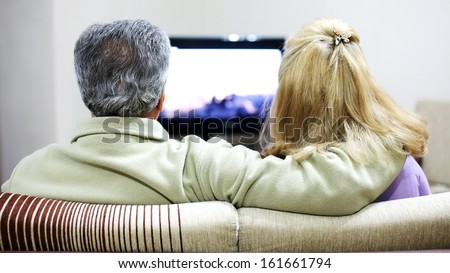 Senior couple sitting together on sofa, watching television  - stock photo