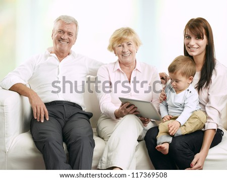 Senior couple sitting with their daughter and grandson. Grandson playing on a digital tablet. - stock photo