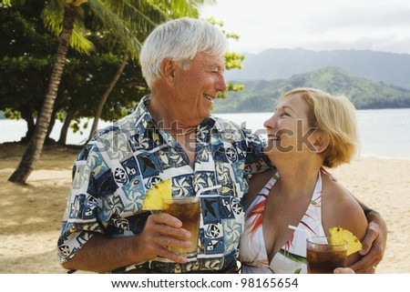 Senior couple smiling at each other in tropical scene - stock photo