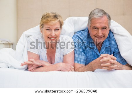 Senior couple smiling under the duvet at home in bedroom - stock photo