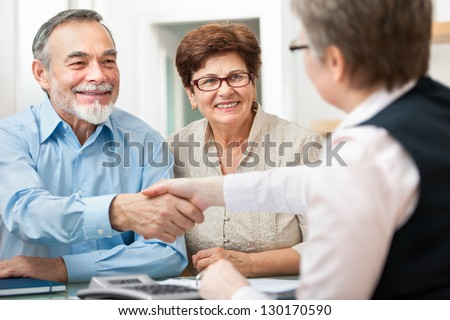 senior couple smiling while shaking hand with financial advisor - stock photo