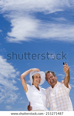 Senior couple standing on beach, man taking photograph with camera phone, smiling, low angle view
